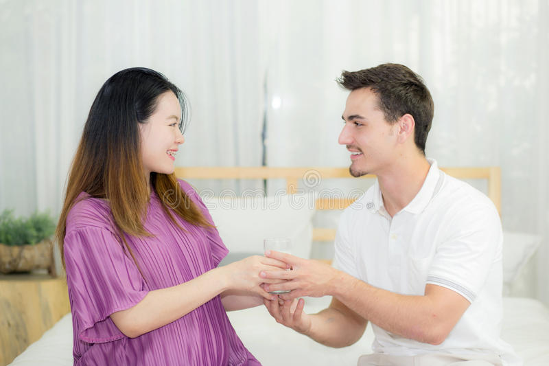 Asian handsome husband takes care about pregnant woman with give a glass of milk. royalty free stock photography