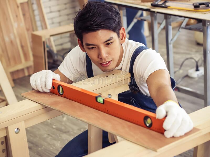 Asian  handsome male carpenter using Water Level Gauge Ruler in the room with wood work.selective focus on a man`s face royalty free stock image