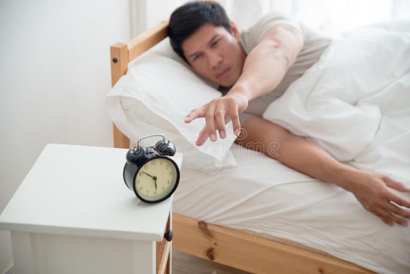 Asian handsome man awakened by alarm clock in the bed at morning time. A man is unhappy from noisy sound of alarm clock and trying to turn it off. Hangover royalty free stock photo
