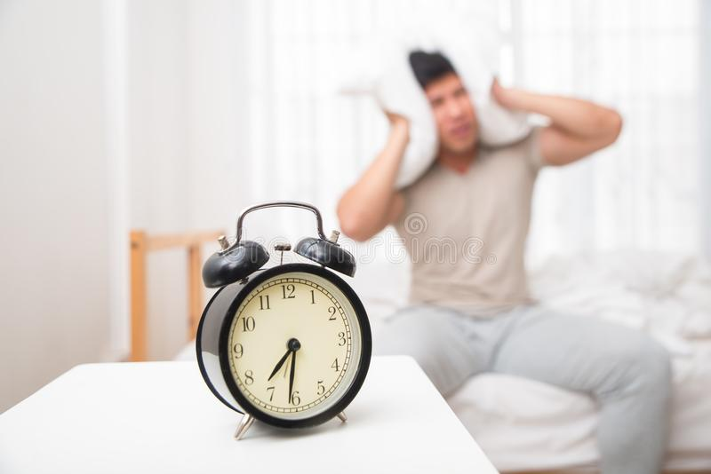 Asian handsome man awakened by alarm clock in the bed at morning time. A man is unhappy from noisy sound of alarm clock and trying to turn it off. Hangover royalty free stock images