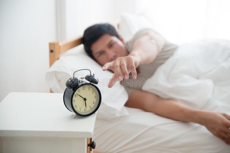 Asian handsome man awakened by alarm clock in the bed at morning time. A man is unhappy from noisy sound of alarm clock and trying to turn it off. Hangover stock photo