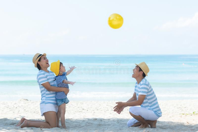 Asian happy family have fun and play yellow ball on the beach.  Family people tourism travel in summer and holiday for destination stock photo