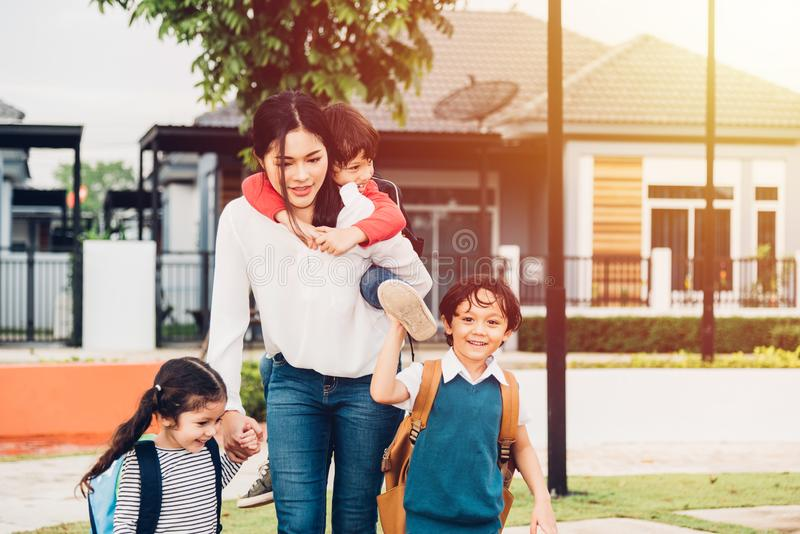 Asian happy mother walking out from home holding hands her kids royalty free stock photos