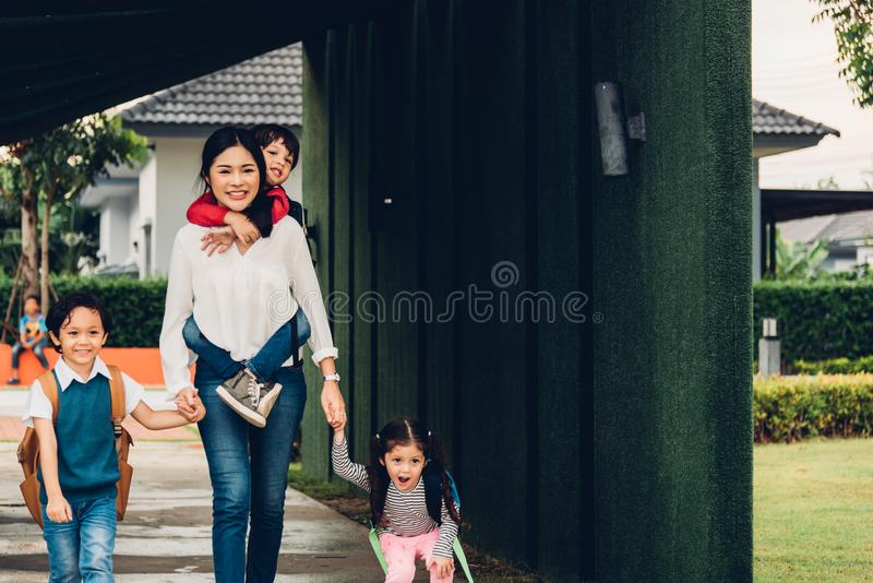 Asian happy mother walking out from home holding hands her kids royalty free stock images