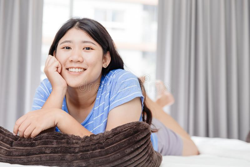 Asian happy teen smiling holiday laying on bed good living healthy at home clean bedroom stock photography