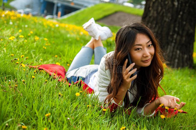 Asian woman calling by phone in summer park on green grass. Asian happy woman calling by phone in summer park on green grass royalty free stock photography