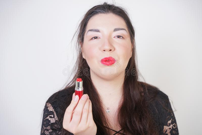 Asian happy woman paints her lips with lipstick on white studio background. Wrong try to do good self make up. Adult girl is learn. Ing to paint her face royalty free stock image