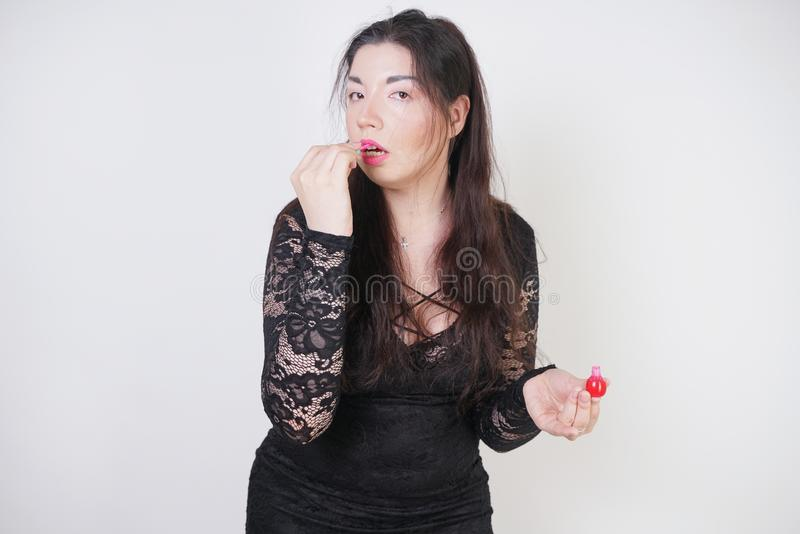 Asian happy woman paints her lips with lipstick on white studio background. Wrong try to do good self make up. Adult girl is learn. Ing to paint her face royalty free stock photo