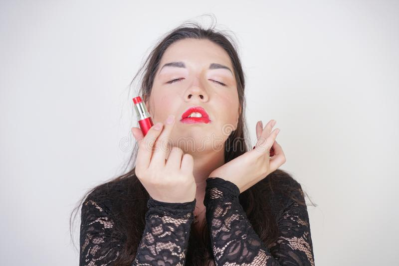 Asian happy woman paints her lips with lipstick on white studio background. Wrong try to do good self make up. Adult girl is learn. Ing to paint her face royalty free stock photos