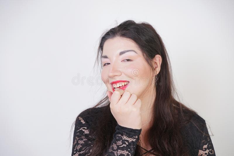 Asian happy woman paints her lips with lipstick on white studio background. Wrong try to do good self make up. Adult girl is learn. Ing to paint her face stock image