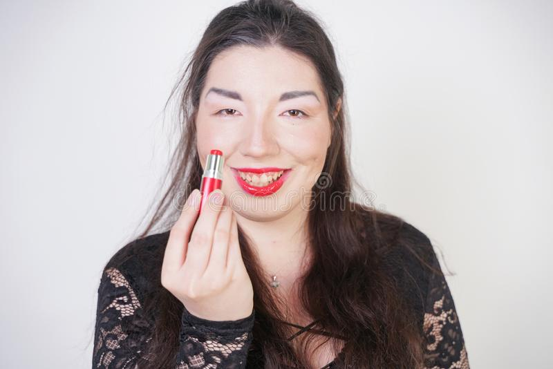 Asian happy woman paints her lips with lipstick on white studio background. Wrong try to do good self make up. Adult girl is learn. Ing to paint her face stock images
