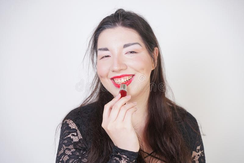 Asian happy woman paints her lips with lipstick on white studio background. Wrong try to do good self make up. Adult girl is learn. Ing to paint her face stock photo