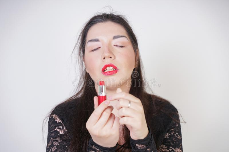 Asian happy woman paints her lips with lipstick on white studio background. Wrong try to do good self make up. Adult girl is learn. Ing to paint her face stock photos