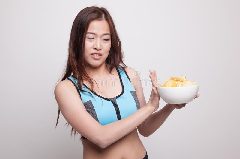 Asian healthy girl hate potato chips, junk food. Asian healthy girl hate potato chips , junk food on white background royalty free stock photography