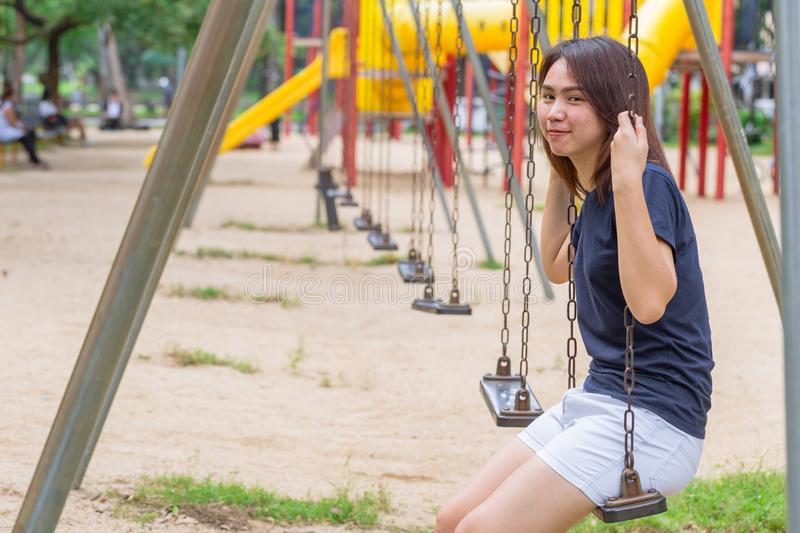 Asian healthy teen wear casual cloth smile sitting play swing royalty free stock photo
