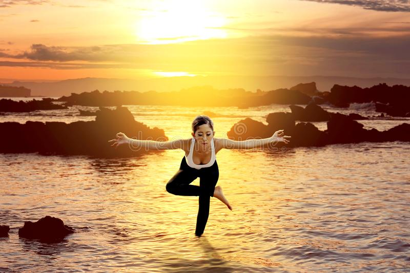 Asian healthy woman practicing yoga on the beach stock image