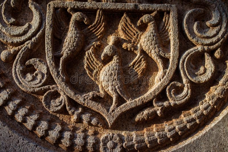 Asian heraldic carved figures in Stone. Close up of heraldic carved figures stock photos