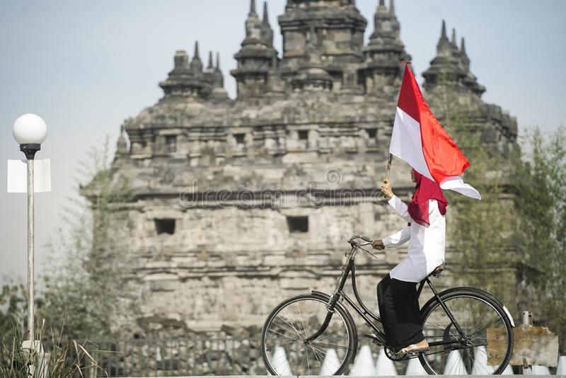 Asian Hijab flapper Indonesian flag in bycycle, Indonesia independence day royalty free stock photography