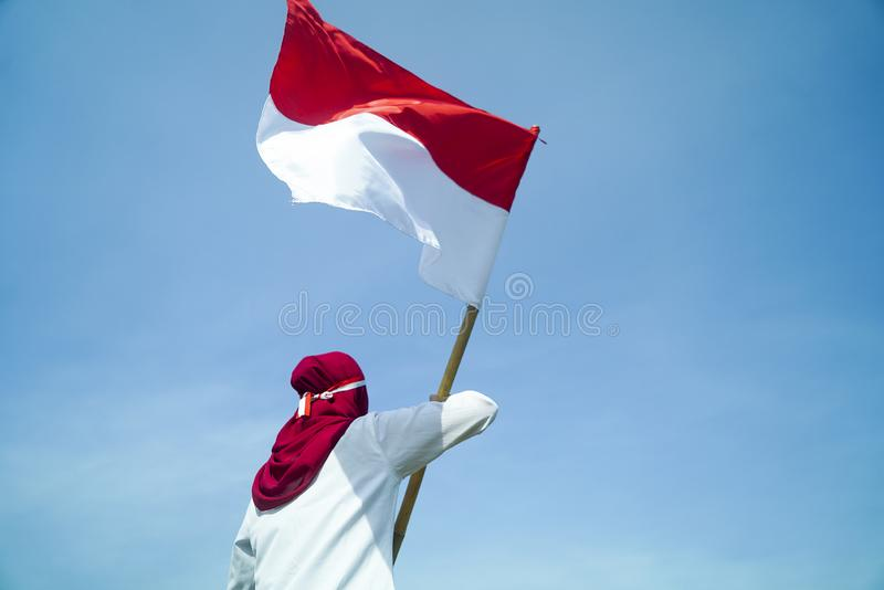 Asian Hijab flapper Indonesian flag with clear blue sky background, Indonesia independence day stock photos