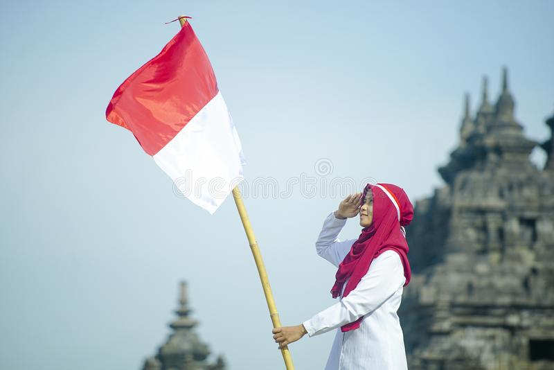 Asian Hijab Holding Indonesian flag with clear blue skyand Plaosan Temple background, Indonesia independence day royalty free stock photos