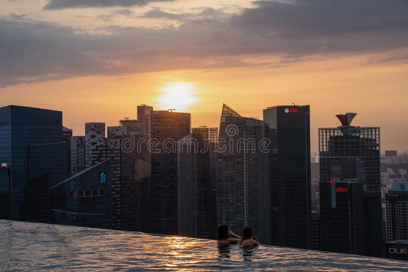 Asian holiday makers enjoying the scenic sunset view of Marina Bay and Singapore business district form the comfort on roof top po royalty free stock photography
