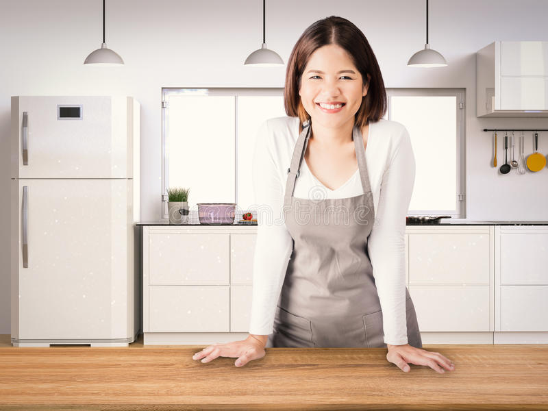 Asian housekeeper. With kitchen background stock photography
