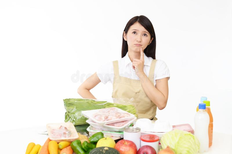 Asian housewife in apron. Housewife thinking what to make for dinner stock photos