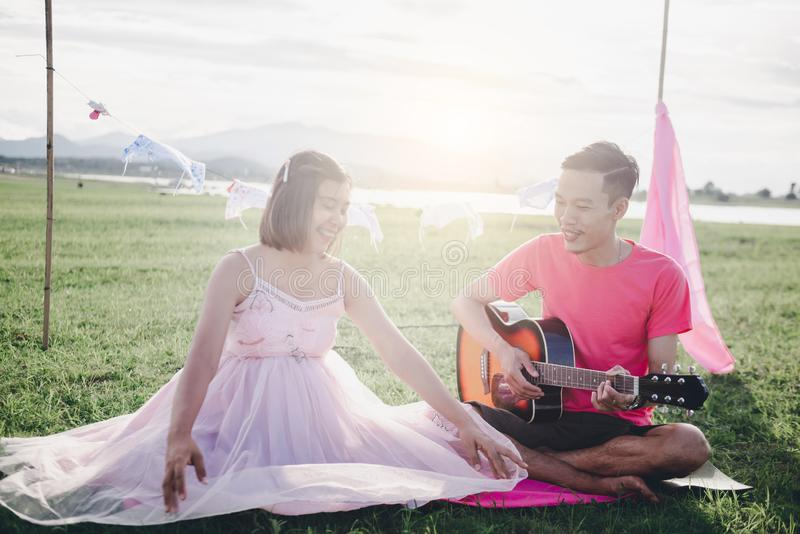 Asian husband playing guitar and enjoy with his pregnant wife outdoor. Asian Married couple and family concept royalty free stock photos
