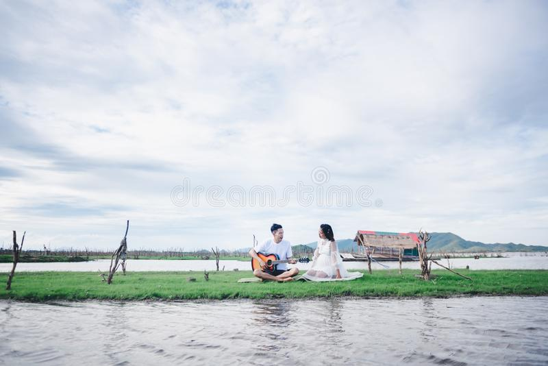 Asian husband playing guitar and enjoy with his pregnant wife outdoor. Asian Married couple and family concept stock photography
