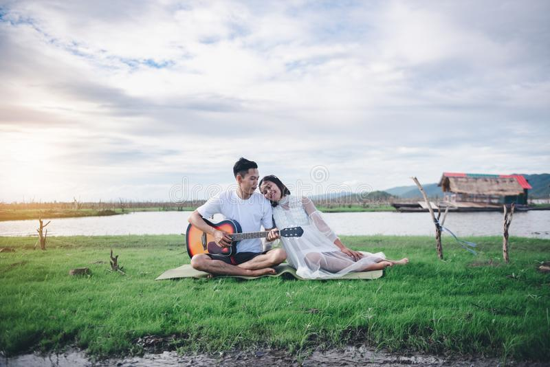 Asian husband playing guitar and enjoy with his pregnant wife outdoor. Asian Married couple and family concept stock photos