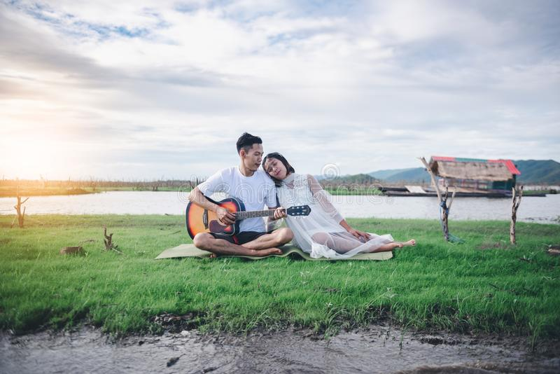 Asian husband playing guitar and enjoy with his pregnant wife outdoor. Asian Married couple and family concept stock photo