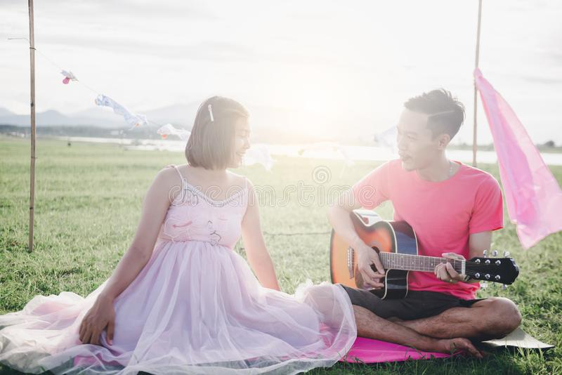 Asian husband playing guitar and enjoy with his pregnant wife outdoor. Asian Married couple and family concept stock image