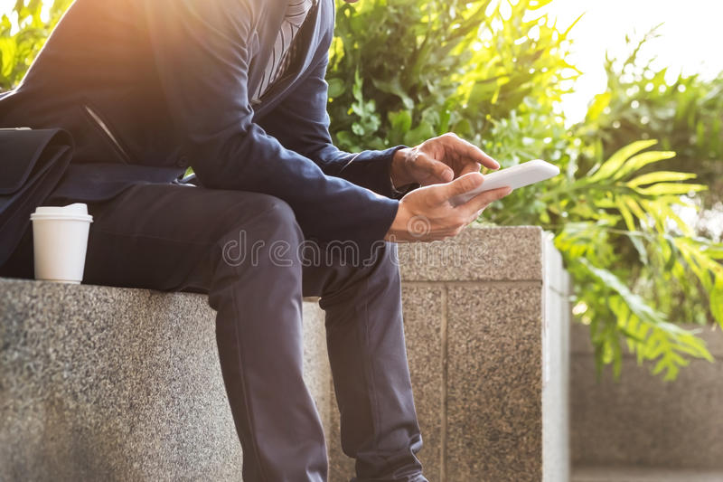 Asian Indian businessman using tablet pc outdoors, golden sunlight background. royalty free stock images