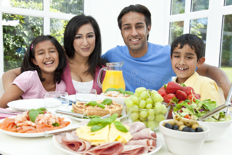 Asian Indian Parents Children Family Eating Food. An attractive happy, smiling Asian Indian family of mother, father, son and daughter eating healthy food & royalty free stock photography
