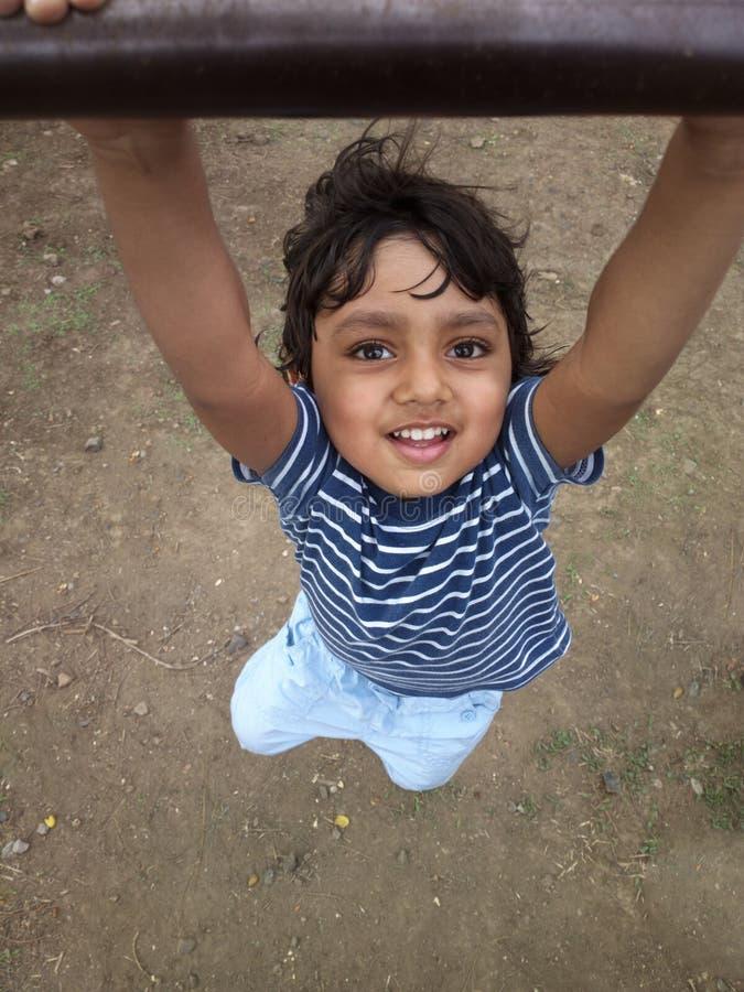 Asian Indian todder boy hanging swing having fun royalty free stock photos