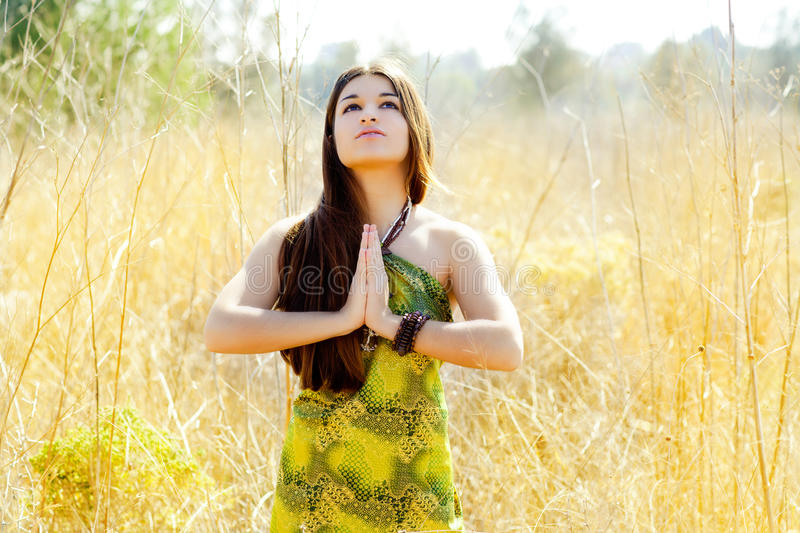 Asian indian woman praying hands in golden field stock images