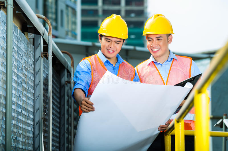 Asian Indonesian construction workers on building site stock image