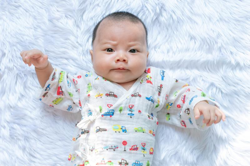 Asian Infant baby is ralaxing on the white bed. It is watching at me. It`s face is frown. royalty free stock image