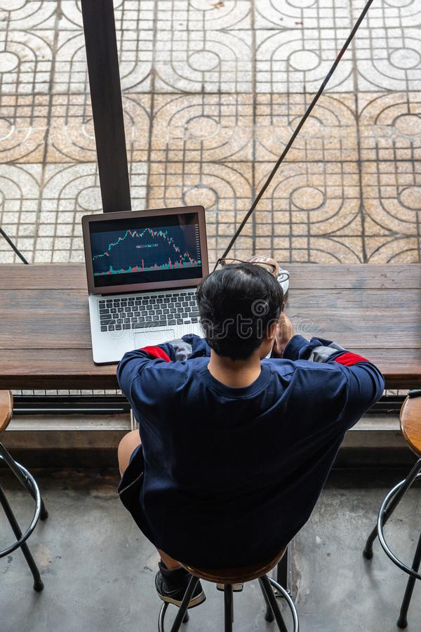 High angle view of Asian investor watching stock trading graph. Asian investor watching stock trading graph on computer at coffeeshop royalty free stock image