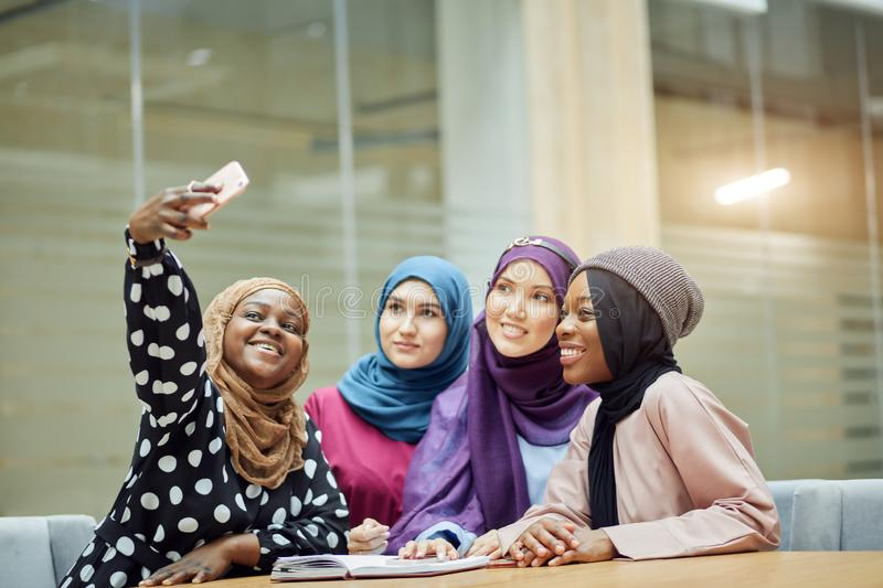 Asian Islamic women sharing info from smartphone during their visit a seminar. Asian Islamic women in bright hijabs sharing info from smartphone during their royalty free stock image
