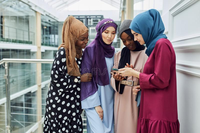 Asian Islamic women sharing info from smartphone during their visit a seminar. Asian Islamic women in bright hijabs sharing info from smartphone during their royalty free stock photo