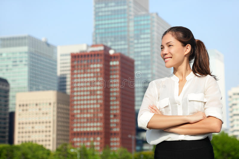 Asian japanese business woman portrait in Tokyo. Happy confident young smart professional in casual business outfit downtown Tokyo with skyline in the stock photography
