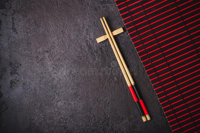 Asian Japanese table setting. Bamboo chopsticks and red black mat on black background.  royalty free stock photos