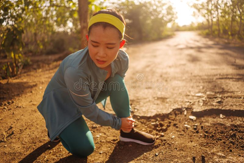 Fitness lifestyle portrait of young attractive Asian Chinese runner woman suffering sport injury during jogging workout on sunset royalty free stock images