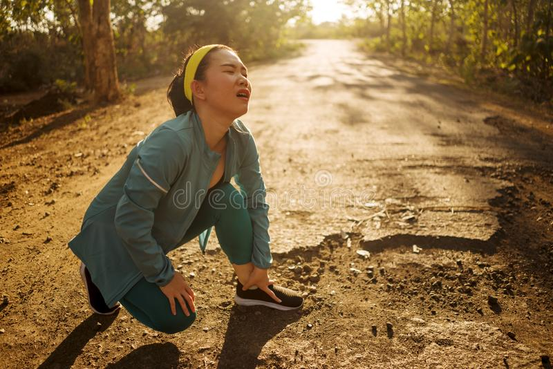Fitness lifestyle portrait of young attractive Asian Korean runner woman suffering sport injury during jogging workout on sunset royalty free stock photography