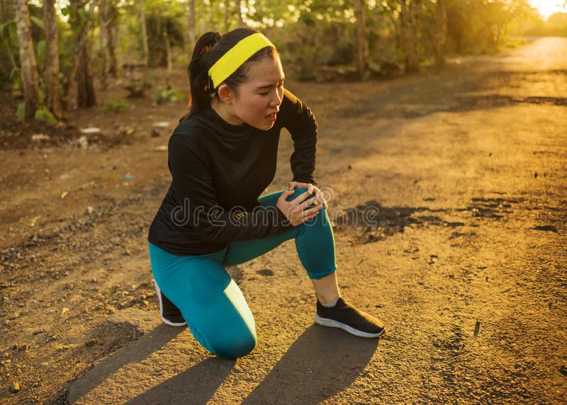 Fitness lifestyle portrait of young attractive Asian runner woman suffering sport injury during jogging workout on sunset road stock photos
