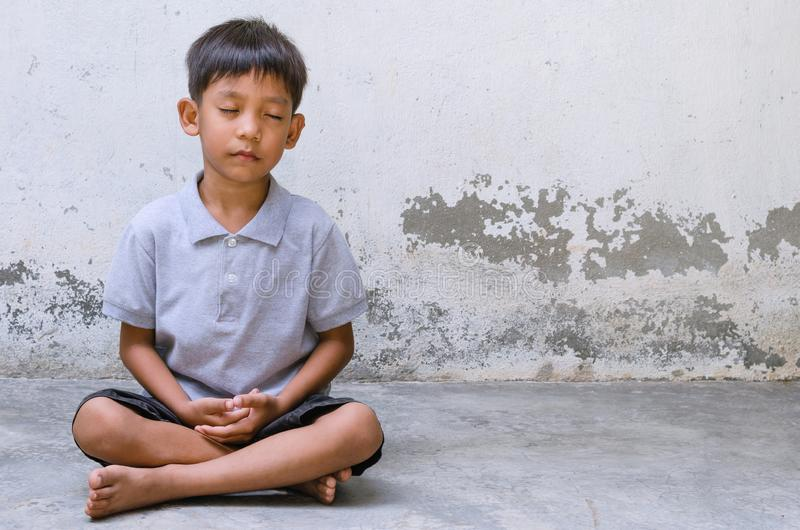 Asian Child Sitting to Meditate. stock photo