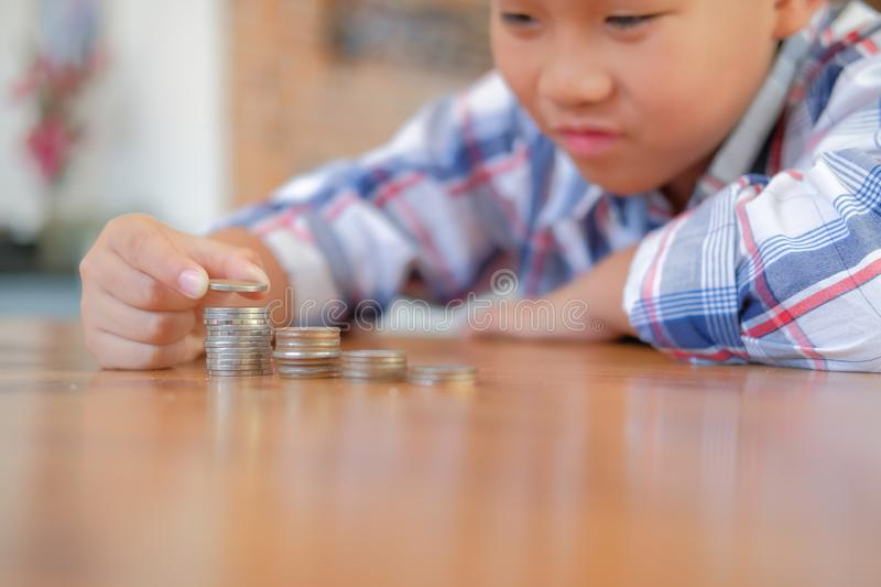 Asian kid boy child children with coins stack pile. money saving. Little asian kid boy child children with coins stack pile. money savings cash deposit for stock photo