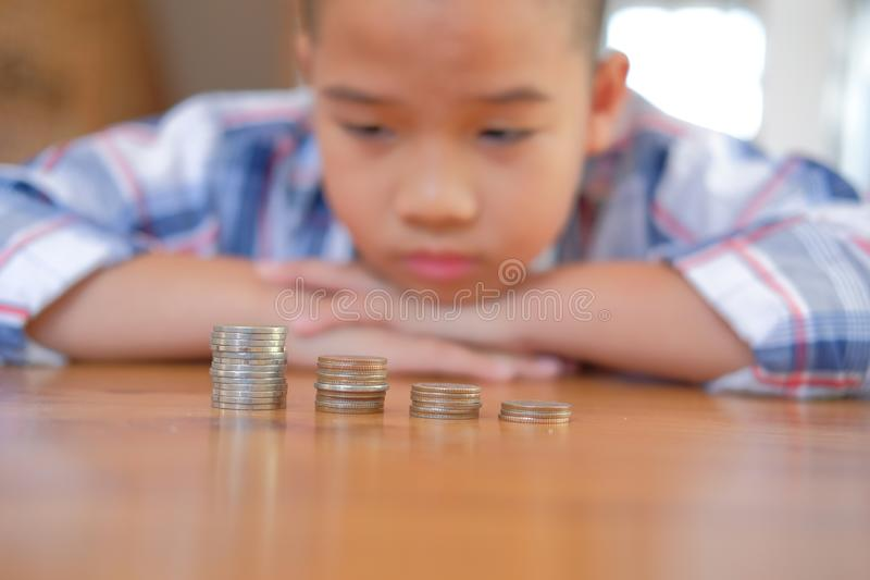 asian kid boy child children with coins stack pile. money saving stock image