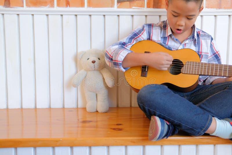 asian kid boy child playing guitar ukulele. children leisure act stock photo